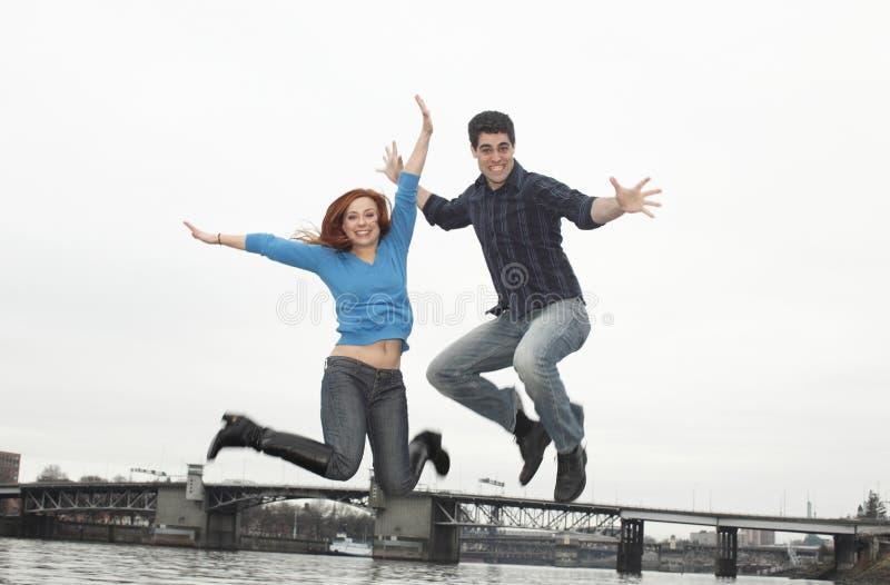 Paar dat in de lucht springt stock fotografie