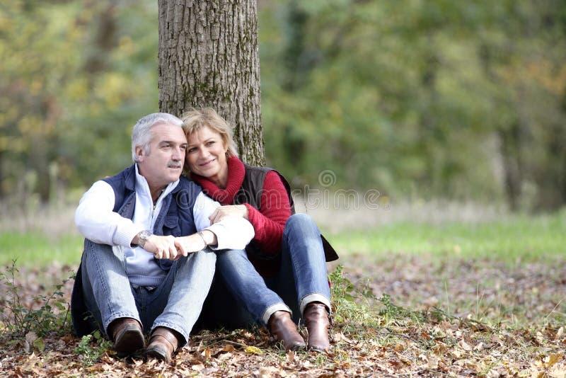 Paar dat door boom wordt gezeten royalty-vrije stock foto