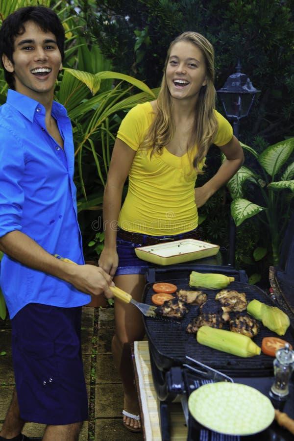Paar dat een openluchtbarbecue heeft stock afbeelding