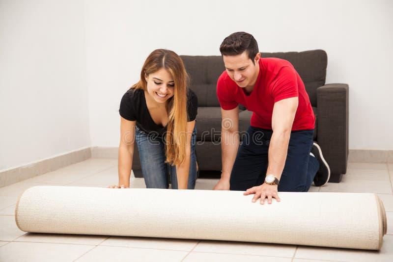 Paar dat een tapijt uitrolt royalty-vrije stock fotografie