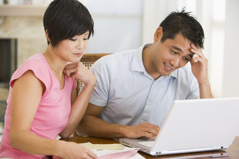 Paar dat in eetkamer met laptop ongelukkig kijkt royalty-vrije stock fotografie