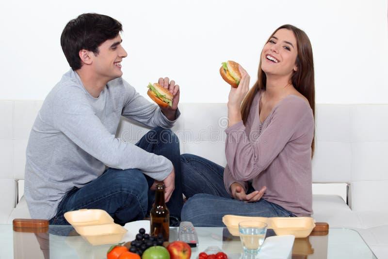 Paar dat hamburgers eet stock afbeeldingen