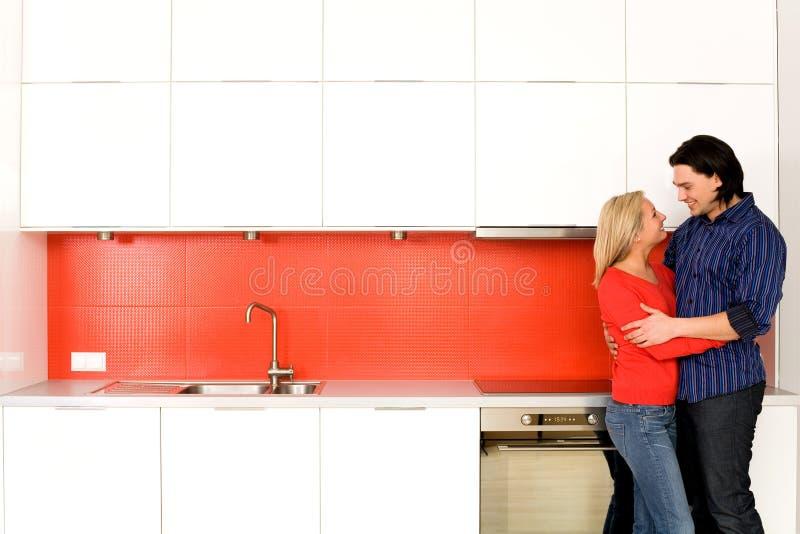 Paar dat in keuken koestert stock foto