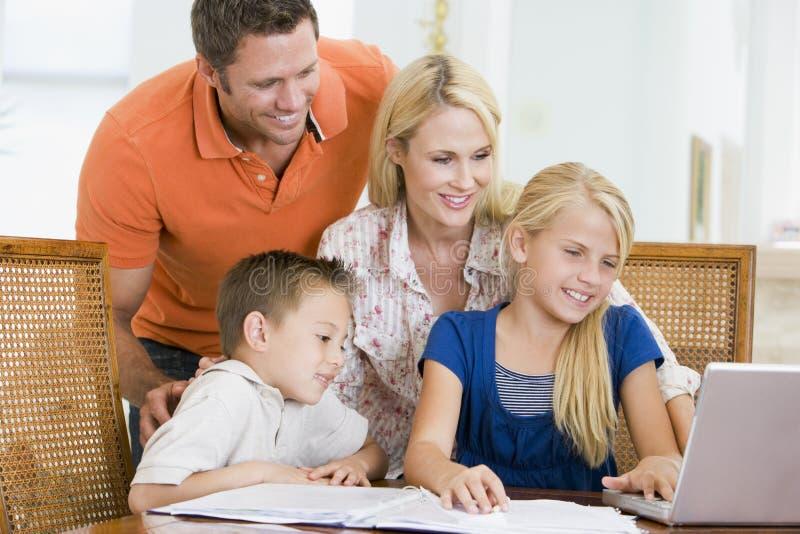 Paar dat kinderen met laptop helpt die thuiswerk doet stock afbeeldingen