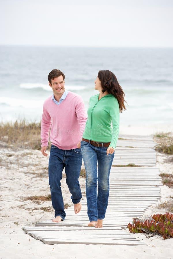 Paar dat langs de holdingshanden van de strandweg loopt stock foto