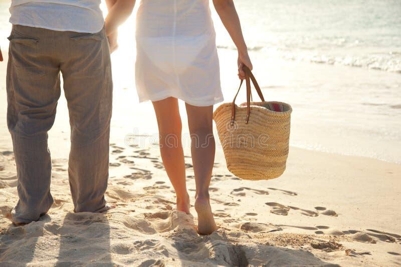 Paar dat langs het strand loopt stock foto