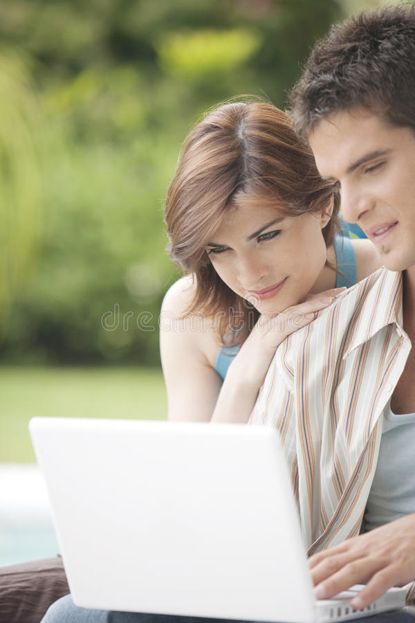 Paar dat Laptop in Tuin met behulp van royalty-vrije stock fotografie