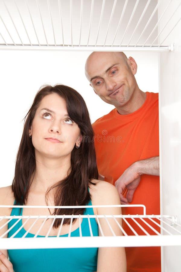 Paar dat in lege koelkast kijkt stock afbeeldingen