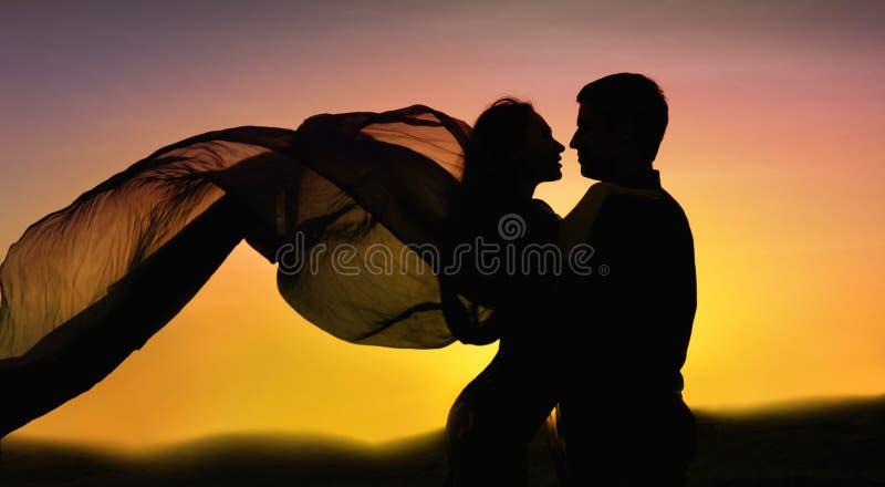 Paar dat in liefde bij zonsondergang danst royalty-vrije stock foto