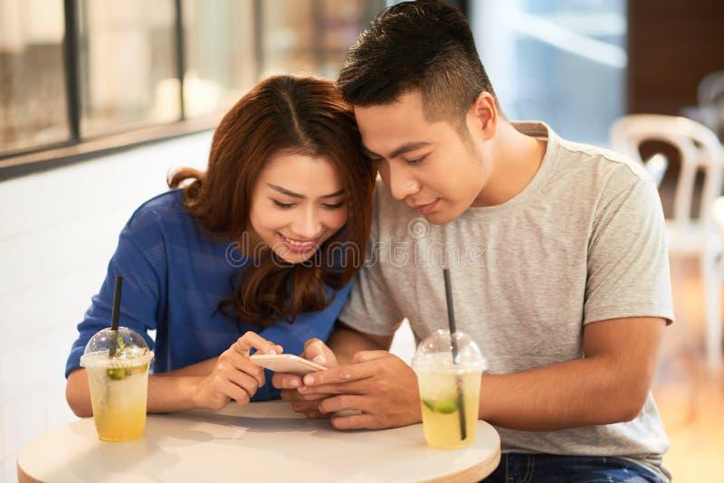 Paar dat mobiele telefoon met behulp van stock afbeelding