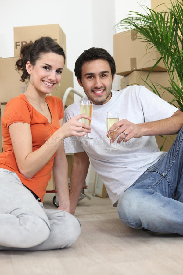 Paar dat in nieuwe flat wordt gezeten stock afbeelding