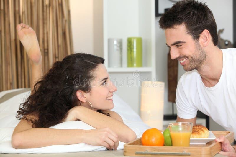 Paar dat ontbijt in bed eet stock foto
