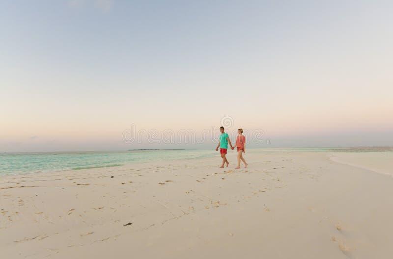 Paar dat op de handen van de strandholding loopt stock foto's