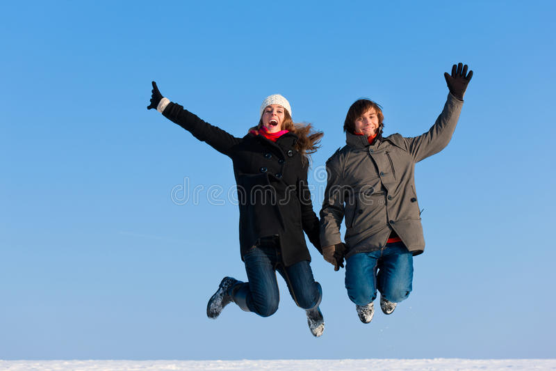 Paar dat op een de winterdag springt stock afbeeldingen
