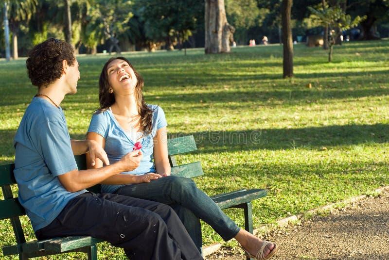 Paar dat op een Horizontale Bank van het Park lacht - stock foto