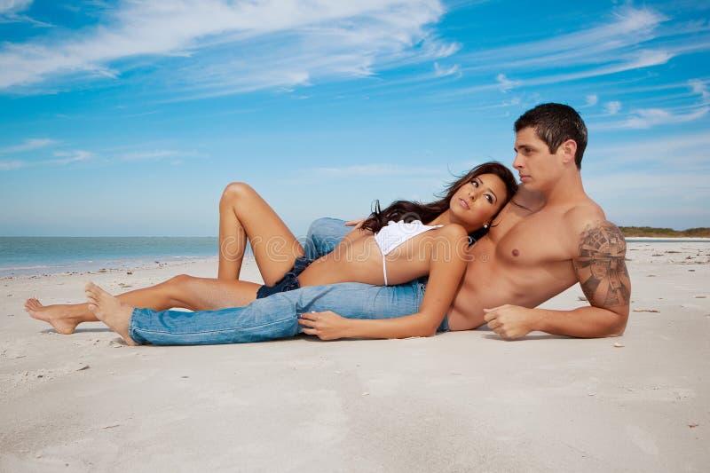 Paar dat op een strand ligt stock afbeeldingen