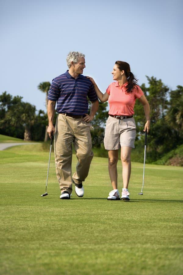 Paar dat op golfcursus loopt stock foto's