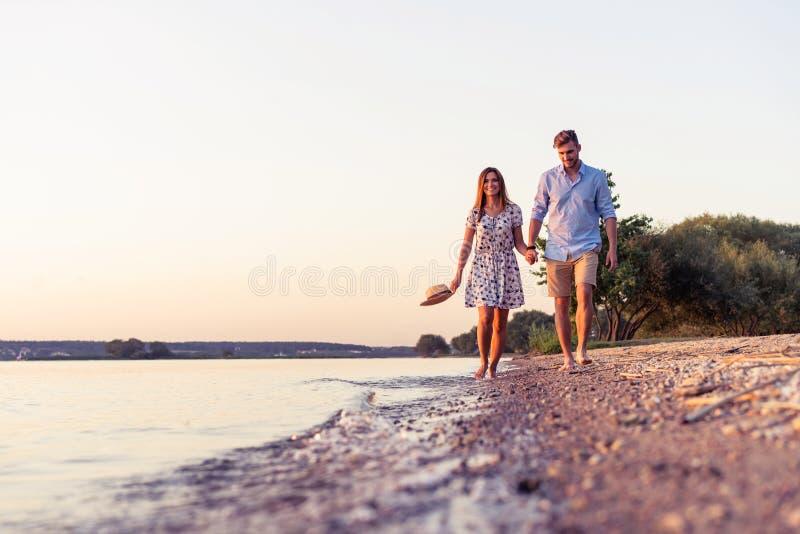 Paar dat op het strand bij zonsondergang loopt stock afbeeldingen