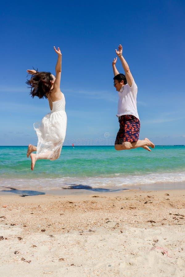 Paar dat op het strand springt stock afbeelding