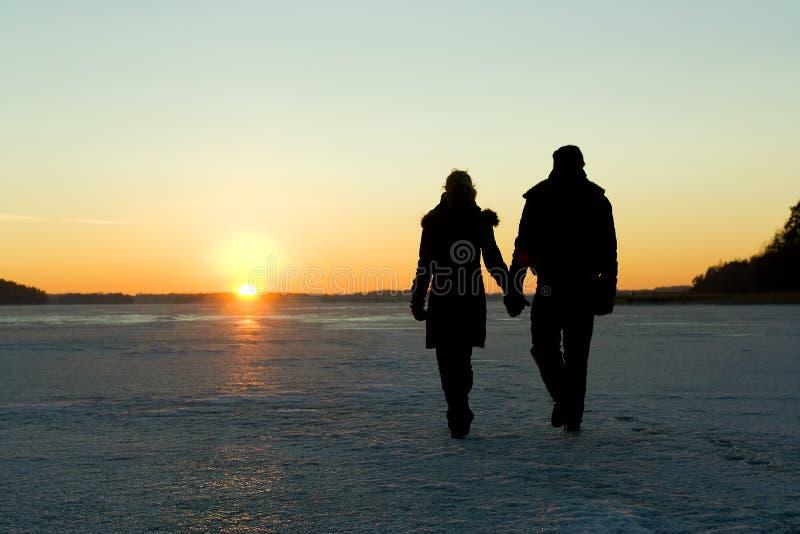 Paar dat op ijs bij zonsondergang loopt stock foto's