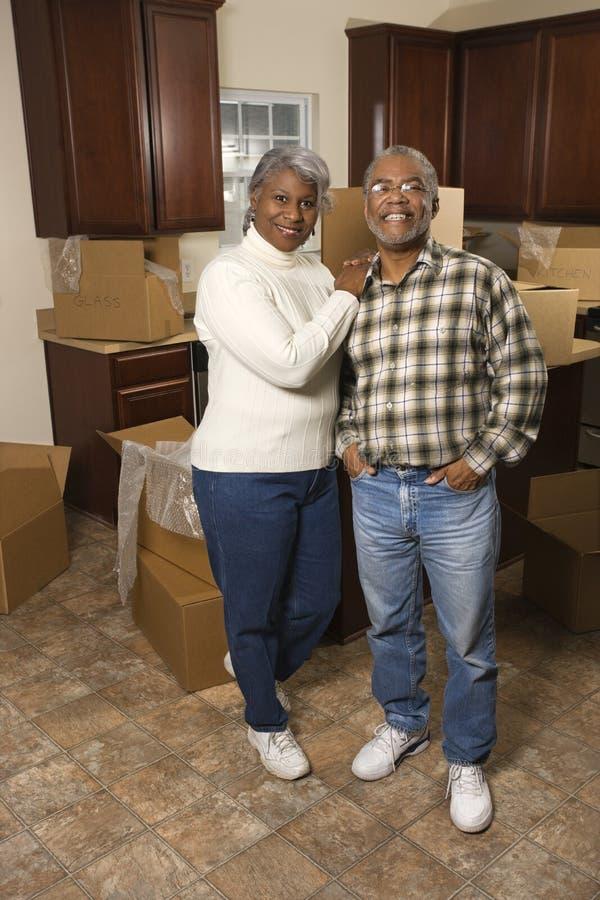 Paar dat op middelbare leeftijd zich in keuken bevindt. royalty-vrije stock fotografie