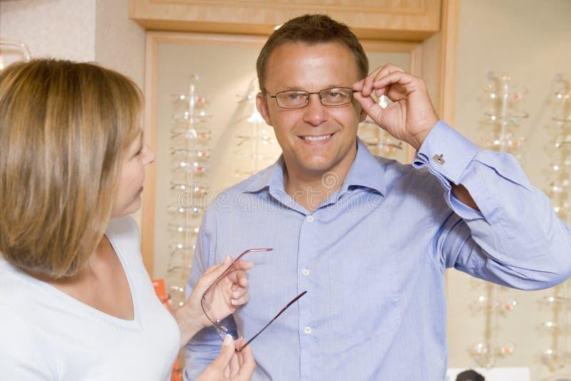 Paar dat op oogglazen bij optometristen probeert stock afbeelding