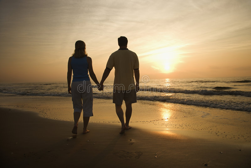 Paar dat op strand bij zonsondergang loopt. stock foto