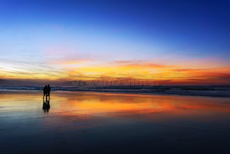 Paar dat op strand bij zonsondergang loopt stock afbeeldingen