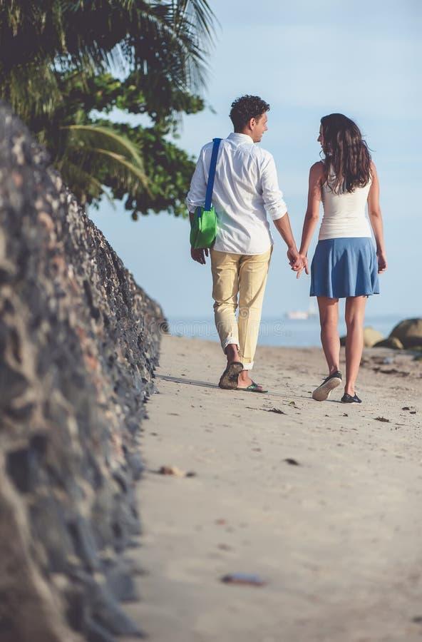 Paar dat op strand loopt dat samen handen houdt royalty-vrije stock fotografie