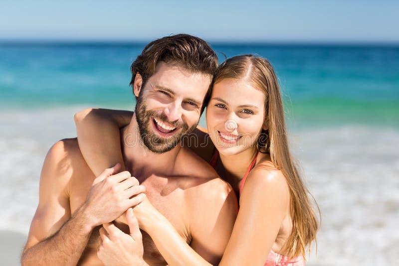 Paar dat op strand omhelst stock fotografie