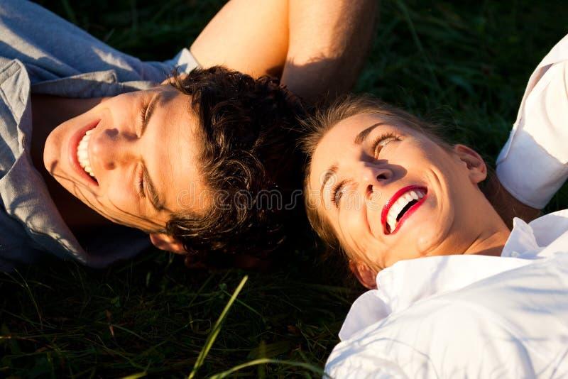 Paar dat op weide in de zonneschijn ligt stock foto