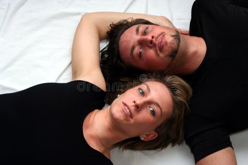 Paar dat op wit legt royalty-vrije stock foto