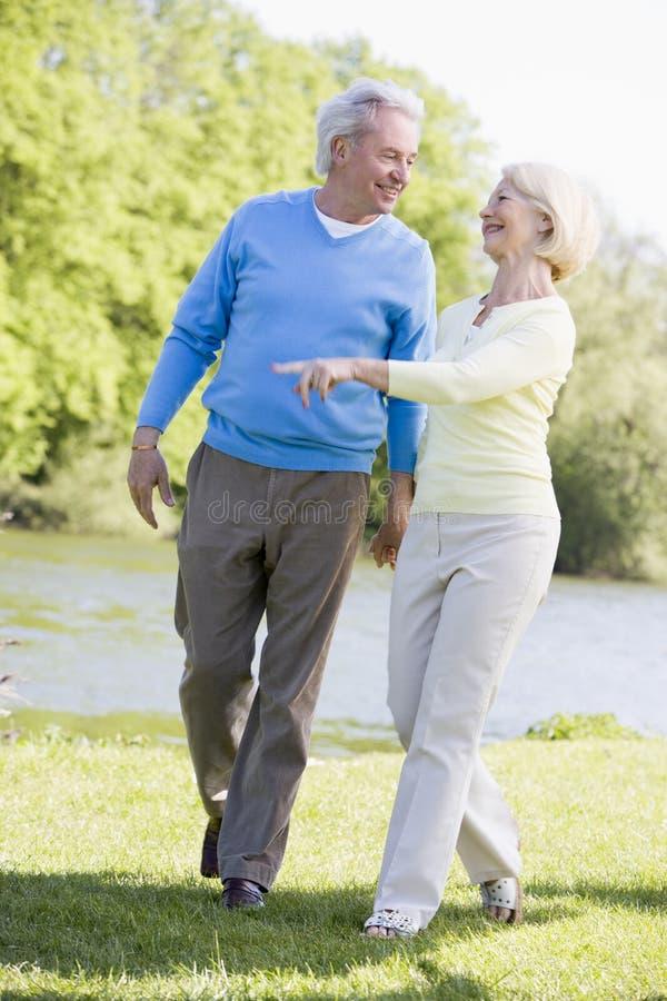 Paar dat in openlucht bij park door meer te glimlachen loopt stock fotografie