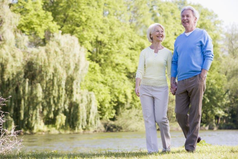 Paar dat in openlucht bij park door meer te glimlachen loopt stock foto