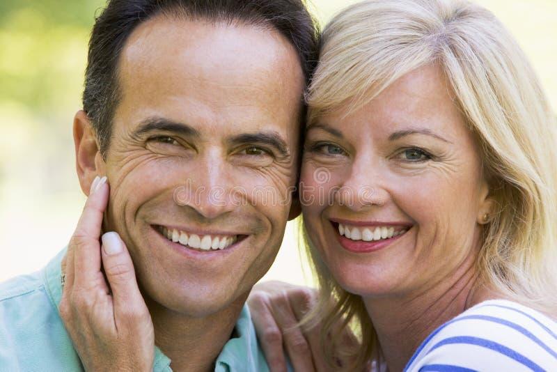 Paar dat in openlucht glimlacht stock fotografie