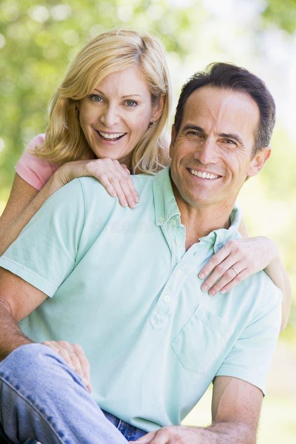 Paar dat in openlucht glimlacht