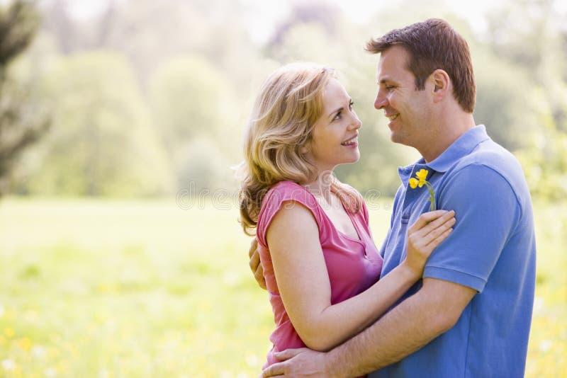 Paar dat in openlucht het houden van bloem het glimlachen omhelst royalty-vrije stock afbeelding