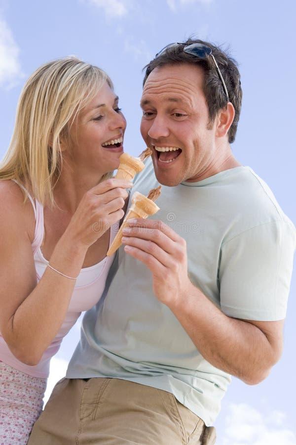 Paar dat in openlucht roomijs en het glimlachen eet stock afbeeldingen