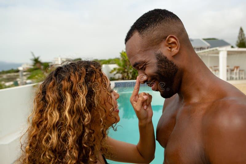 Paar dat pret dichtbij zwembad heeft bij de binnenplaats van huis royalty-vrije stock fotografie