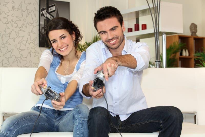 Paar dat pret het spelen videospelletjes heeft stock foto's