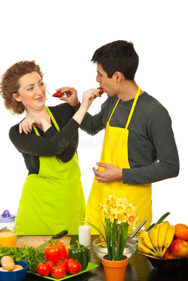 Paar dat pret met aardbeien heeft stock foto's