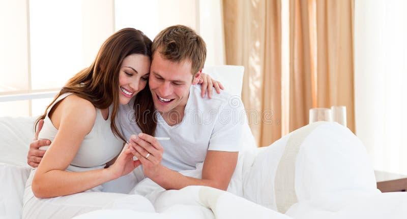 Paar dat resultaten van een zwangerschapstest te weten komt stock afbeelding