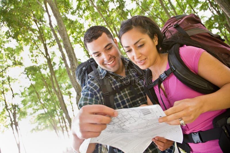 Paar dat in rugzakken kaart bekijkt stock fotografie