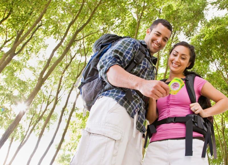Paar dat in rugzakken kompas bekijkt royalty-vrije stock foto