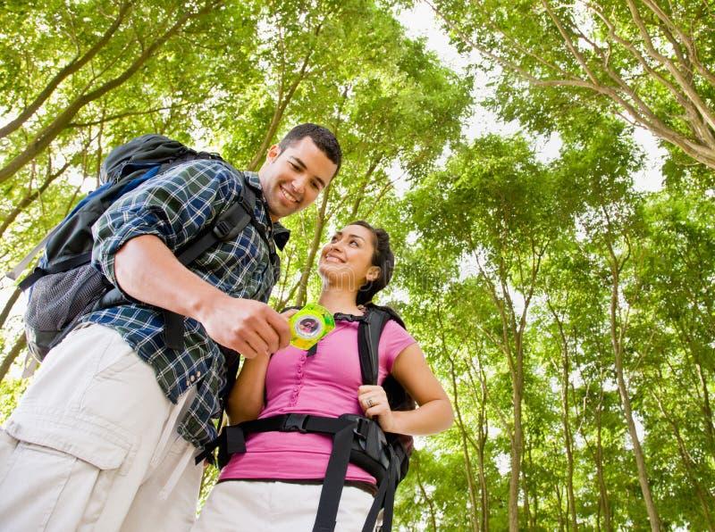 Paar dat in rugzakken kompas bekijkt stock foto