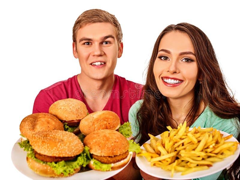 Paar dat snel voedsel eet De man en de vrouw eten hamburger royalty-vrije stock afbeeldingen