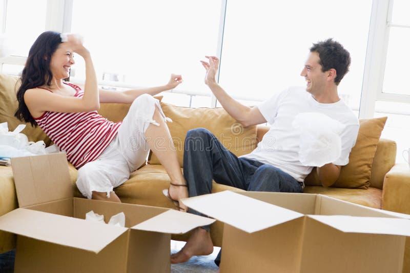 Paar dat speels dozen in nieuw huis uitpakt stock foto's