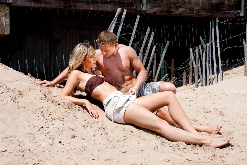 Paar dat in zand legt royalty-vrije stock afbeelding