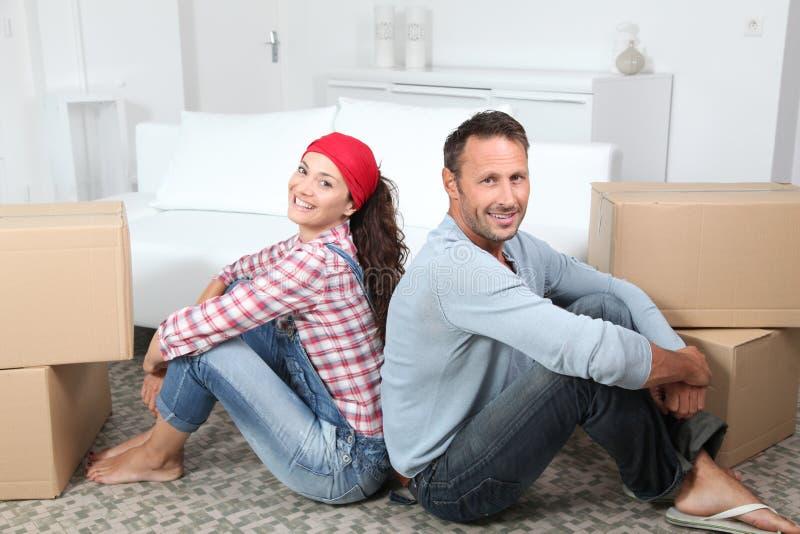 Paar dat zich in nieuw huis beweegt stock afbeelding