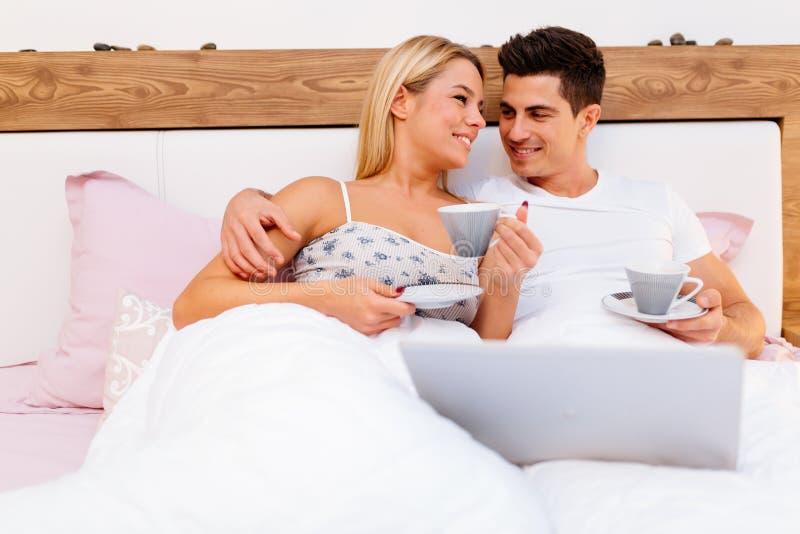 Paar in de koffie van de liefdeholding terwijl in bed royalty-vrije stock afbeeldingen